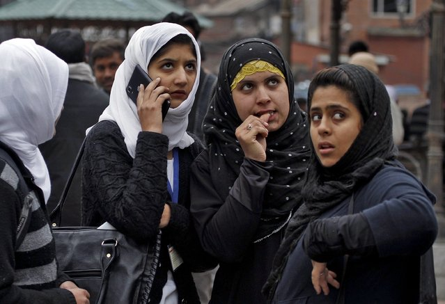 Kashmiri girls stand on a road divider after vacating their office buildings following an earthquake in Srinagar October 26, 2015. An earthquake measuring 7.6 magnitude struck in northeastern Afghanistan on Monday, the U.S. Geological Survey said, sending tremors that were felt in India and Pakistan. (Photo by Danish Ismail/Reuters)