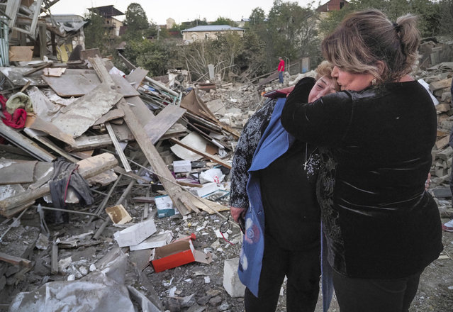 A neighbour comforts home owner, Lida Sarksyan, left, near her house destroyed by shelling from Azerbaijan's artillery during a military conflict in Stepanakert, the separatist region of Nagorno-Karabakh, Saturday, October 17, 2020. The latest outburst of fighting between Azerbaijani and Armenian forces began Sept. 27 and marked the biggest escalation of the decades-old conflict over Nagorno-Karabakh. The region lies in Azerbaijan but has been under control of ethnic Armenian forces backed by Armenia since the end of a separatist war in 1994. (Photo by AP Photo/Stringer)