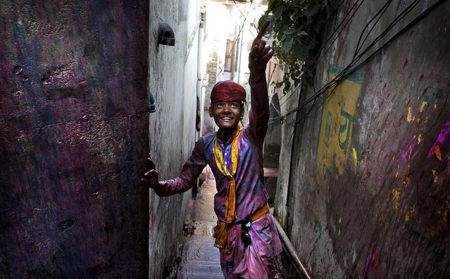 A young villager from Nandgaon, soaked in water and colors, arrives in Barsana. (Photo by Manish Swarup/Associated Press)
