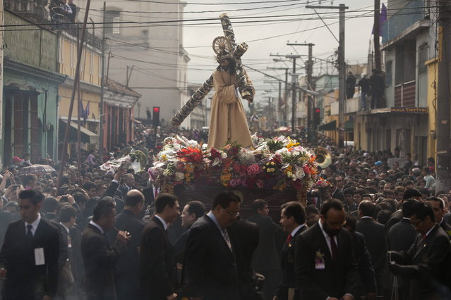 """Parishioners parade the Jesús Nazareno de la Merced statue through downtown Guatemala City, in the annual Holy Tuesday procession known as """"La Reseña"""",  March 26, 2013. La Reseña or Review is one of the country's earliest Catholic processions, the first recorded in 1721. (Photo by Moises Castillo/AP Photo)"""