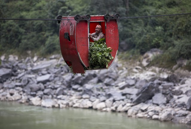 Nepalese farmer Barta Bahadur Rai, aged 67, crosses the Trishuli River using a rope bridge, known locally as a Tuin,  near the village of Fhading Village in Dhading Disrict, some 90 kilometers from capital Kathmandu, Nepal. 04 December 2014. (Photo by Narendra Shrestha/EPA)
