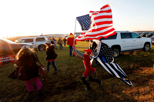 A young woman plays with flags as supporters of US President Donald Trump arrive to attend his final Make America Great Again rally of the 2020 US Presidential campaign at Gerald R. Ford International Airport on November 2, 2020, in Grand Rapids, Michigan. (Photo by Jeff Kowalsky/AFP Photo)
