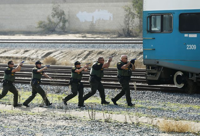 Sheriff officers from San Diego's North County Transit District approach a commuter train while training for an active shooter scenario onboard a train in Oceanside, California December 10, 2014. (Photo by Mike Blake/Reuters)