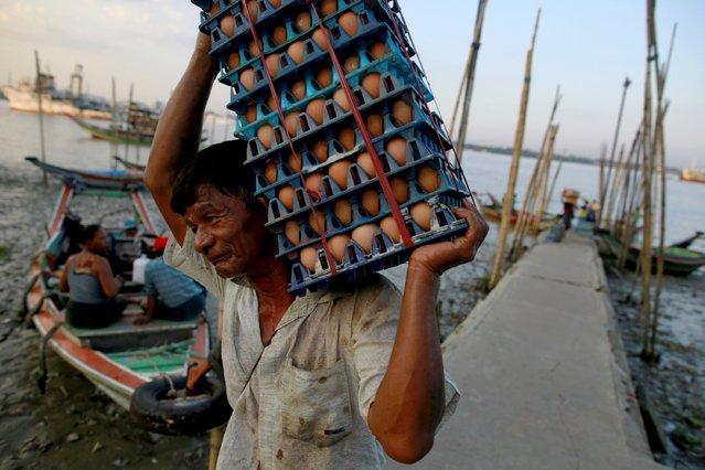 A man unload eggs from a boat in Dala, across Yangon October 23, 2015. (Photo by Soe Zeya Tun/Reuters)