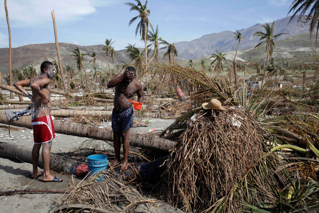 Men take a bath next to trees downed by Hurricane Matthew in Coteaux, Haiti, October 9, 2016. (Photo by Andres Martinez Casares/Reuters)