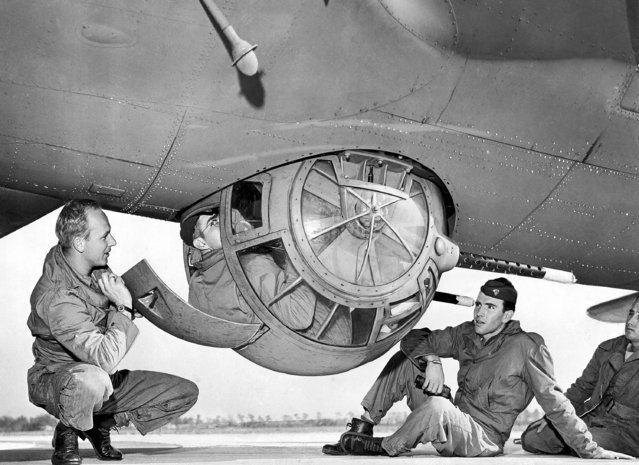 Private Harold L. Langhofer edges into the ball-turret, March 9, 1943. Curled in this position, he can turn the turret so that it fires in any direction. The turret can also be swung around so that the hatch opens into the plane, and the gunner can crawl into it while the Flying Fortress is in motion. (Photo by AP Photo)