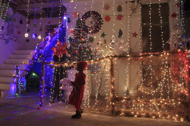 A girl stands outside a house illuminated with lights on Christmas eve in a Christian slum in Islamabad December 24, 2014. (Photo by Faisal Mahmood/Reuters)