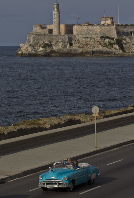In this October 15, 2014 photo, tourists ride in a classic American car on the Malecon in Havana, Cuba. (Photo by Franklin Reyes/AP Photo)
