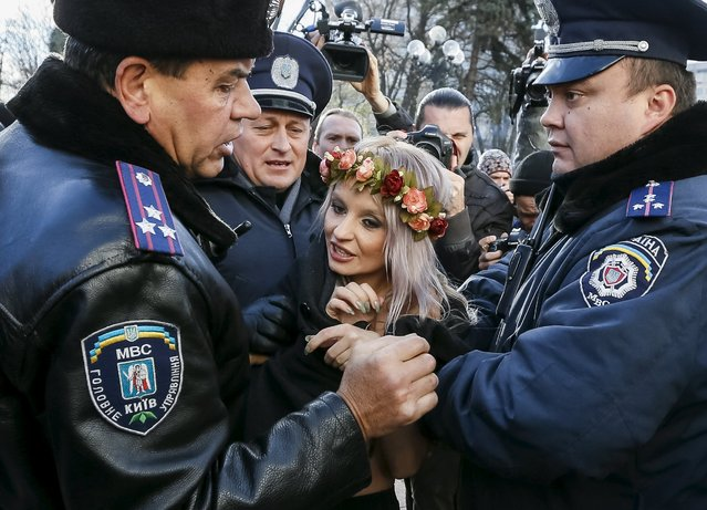 Ukrainian police detain an activist of women's rights group Femen as she protests against homophobia outside the parliament building in Kiev, Ukraine, November 12, 2015. (Photo by Gleb Garanich/Reuters)