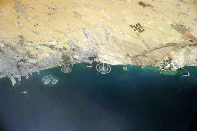 Artificial islands, Dubai, United Arab Emirates, as seen from the International Space Station (ISS). The two palm islands are Palm Jumeirah (centre left, started 2001) and Palm Jebel Ali (centre, started 2006). The World Islands (further to the left, started 2003) depict a world map. (Photo by NASA/SPL/Barcroft Media)