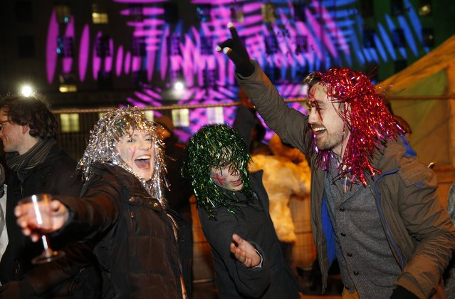 Revellers from London dance as they wait for fireworks to start at the London Eye on the River Thames during New Year celebrations in London December 31, 2014. (Photo by Suzanne Plunkett/Reuters)