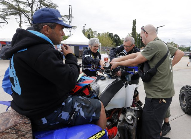 Sergio Lafuente of Uruguay looks at technicians placing GPS on his Yamaha quad ahead of the Dakar Rally 2015 in Buenos Aires January 1, 2015. (Photo by Enrique Marcarian/Reuters)