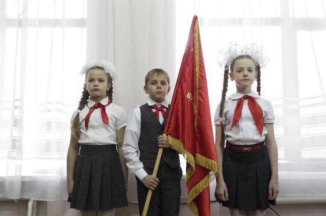 Children, wearing red neckerchiefs, a symbol of the Pioneer Organization, attend a ceremony for the inauguration of 18 new members at a local school in the southern settlement of Kazminskoye in Stavropol region, Russia, November 19, 2015. (Photo by Eduard Korniyenko/Reuters)