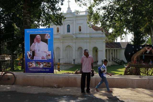 In this Tuesday, January 6, 2015 photo, Sri Lankans walk past a poster to welcome Pope Francis outside a church in Moratuwa, on the outskirts of Colombo, Sri Lanka. (Photo by Eranga Jayawardena/AP Photo)