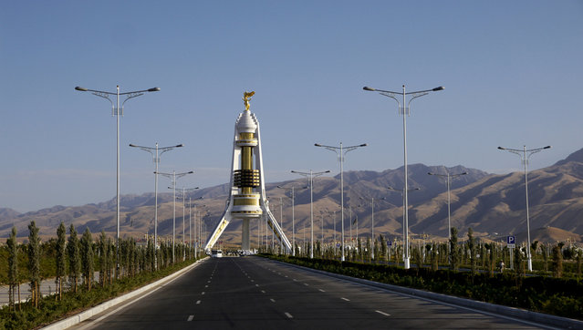 The Monument to Neutrality featuring (and erected by) former president Saparmurat Niyazov. Public buses are routed up an eight-lane boulevard to its base, otherwise it stands mostly deserted. Despite the scarcity of visitors, soldiers at the feet of the structure stand at attention throughout the day. (Photo by Amos Chapple via The Atlantic)
