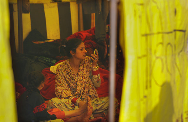 A newly wed woman looks in a mirror as she joins her farmer husband for a protest in a makeshift tent in one of the three main protest sites outside New Delhi's border, India, Friday, February 5, 2021. (Photo by Manish Swarup/AP Photo)