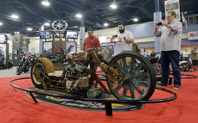 Visitors photograph at a custom made motorcycle, Friday, January 16, 2015, at a motorcycle show at the Miami Beach Convention Center in Miami Beach, Fla. The world's leading manufacturers will be on hand to display their North American lineups in Miami Beach. (Photo by Alan Diaz/AP Photo)