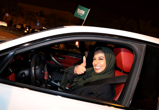 A Saudi woman celebrates as she drives her car in her neighborhood, in Al Khobar,  Saudi Arabia on June 24, 2018. Saudi Arabia had a blanket ban on women driving, with those caught behind the wheel detained. The strict rules in the Islamic country were enforced despite neither Islamic or Saudi law explicitly prohibiting women from driving. The ban had the backing of powerful ultraconservative clerics who argued such acts would corrupt society and lead to sin. One cleric even claiming getting behind the wheel could damage women's ovaries and damage fertility. For decades women drivers have faced arrest and harassment with several high profile protests. In 1990 a major protest saw 50 women drivers travel through the streets of the country's capital, Riyadh. They were arrested and lost their passports and jobs. In 2011 a woman was sentenced to 10 lashes for driving - although the late King Abdullah overturned the sentence. A royal order in 2017 decreed that both women and men should be issued driving licences. The change came into force in June 2018. (Photo by Hamad I Mohammed/Reuters)