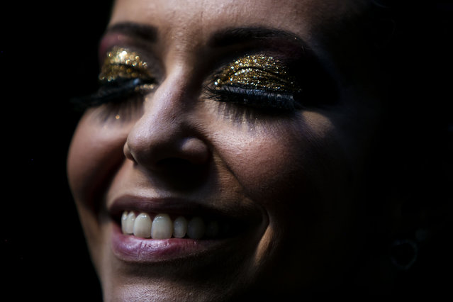 """A member of the """"Desliga da Justica"""" street band gets dressed in her costume in Rio de Janeiro, Brazil, Sunday, February 14, 2021. The group's performance was broadcast live on social media for those who were unable to participate in the carnival due to COVID restrictions after the city's government officially suspended Carnival and banned street parades or clandestine parties. (Photo by Bruna Prado/AP Photo)"""
