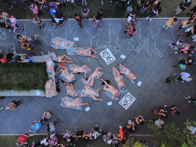 """Female protesters lie on a sidewalk covered in plastic bags in protest against gender violence, in Buenos Aires, Argentina, Wednesday, February 17, 2021. Women from the """"Ni Una Meno"""" or """"Not One Les"""" movement marched to protest what they say is the negligence of judges when it comes to taking measures against aggressors of women, a week after the killing of Ursula Bahillo, a woman who had filed more than a dozen complaints against the man who killed her. She had filed the last complaint two days before her murder. (Photo by Natacha Pisarenko/AP Photo)"""