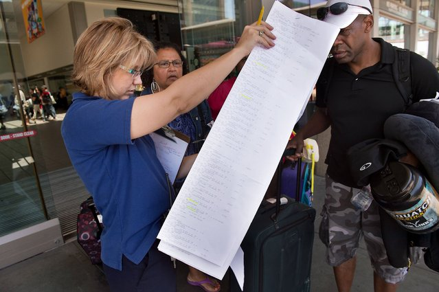 US Airways Escort Denice Miracle, left, pours over a list of passengers to be put on a bus to San Francisco at the Sacramento International Airport in Sacramento, California, on Saturday, July 6, 2013. The travelers were diverted to Sacramento after an Asiana Airlines Boeing 777 crashed on landing at San Francisco International Airport. (Photo by Randall Benton/Sacramento Bee/MCT)