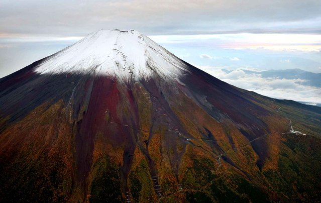 A photo shows snow observed on top of Mt. Fuji on Sunday afternoon for the first time this autumn from a Yomiuri Shimbun helicopter on October 11, 2015. According to the Kofu Meteorological Office, this year's first snow on the 3,776-meter highest mountain is five days earlier than last year and 11 days later than in the average year. (Photo by The Yomiuri Shimbun via AP Images)