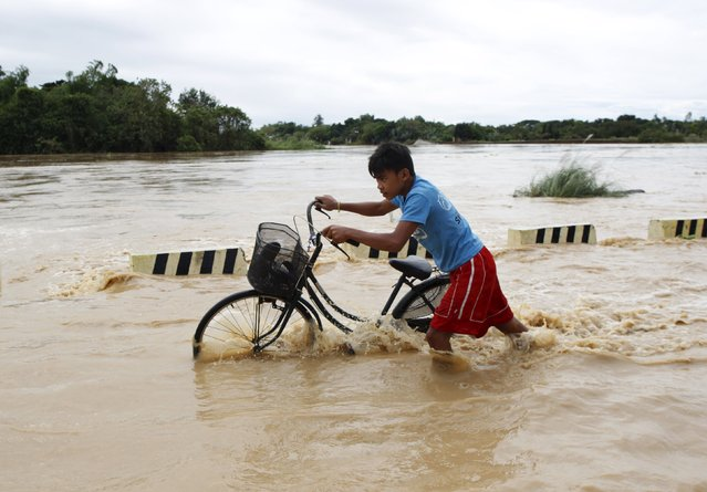 A boy pushes his bicycle through a flooded road after heavy rain at Candaba town, Pampanga province, north of Manila, December 17, 2015. (Photo by Czar Dancel/Reuters)