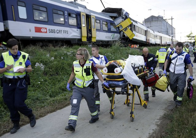 Swiss rescue workers wheel a wounded person on a stretcher after two regional trains crashed head on near Granges-Pres-Marnand near Payerne in western Switzerland July 29, 2013. The two trains collided in the Swiss canton of Vaud on Monday evening, injuring about 40 people, four seriously, Swiss news agency ATS reported. There was no immediate report of any deaths in the crash. (Photo by Denis Balibouse/Reuters)