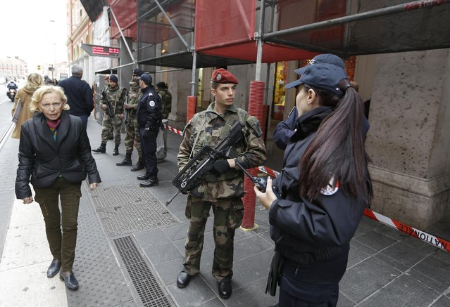 Soldiers and police officers stand guard after an attacker with a knife hidden in his bag attacked three soldiers on an anti-terror patrol in front of a Jewish community center in Nice, southern France, Tuesday February 3, 2015. (Photo by Lionel Cironneau/AP Photo)