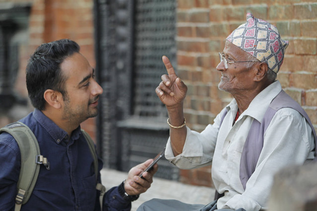 In this Monday, October 17, 2016 photo, Nepalese photographer Jay Poudyal chats with an elderly man in Kathmandu, Nepal. (Photo by Niranjan Shrestha/AP Photo)