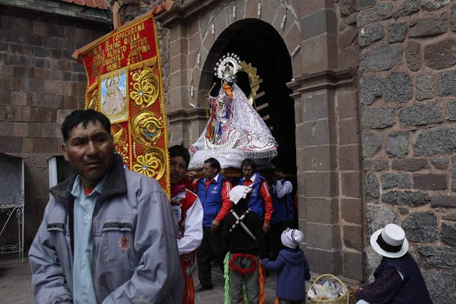 """In this Sunday, August 5, 2018 photo, """"cargadores"""" or male carriers exit the Almudena Temple shouldering a statue of Our Lady of Copacabana, where a service was held in the virgin's honor, in Cuzco, Peru. After lunch and some dancing, the carriers returned the statue to the home of local resident Libia Espinoza, who received the religious icon more than a decade ago as a gift while visiting Bolivia. (Photo by Martin Mejia/AP Photo)"""