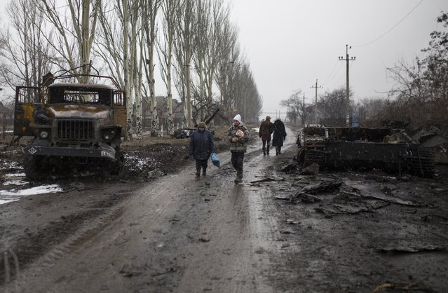 Residents walk in a street in the town of Vuhlehirsk, eastern Ukraine, Tuesday, February 10, 2015. Fighting in eastern Ukraine intensified on Tuesday ahead of much-anticipated peace talks, with both sides claiming significant advances. (Photo by Vadim Braydov/AP Photo)