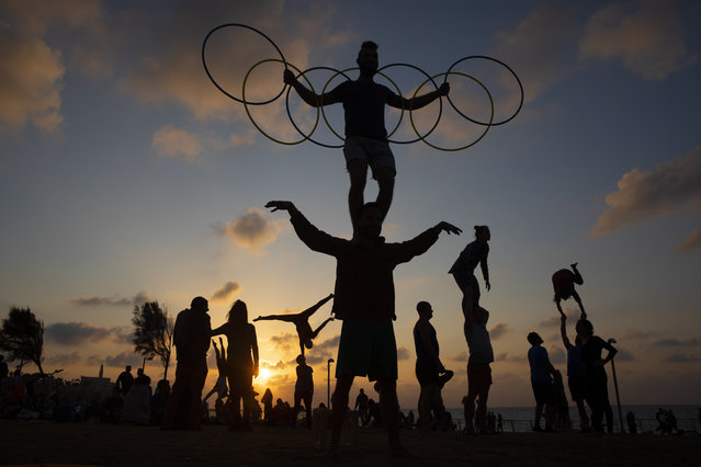 Acrobats perform gymnastic stunts as they work out during a nationwide lockdown to curb the spread of the COVID-19 virus at a park in Tel Aviv, Israel, Saturday, February 6, 2021. (Photo by Oded Balilty/AP Photo)