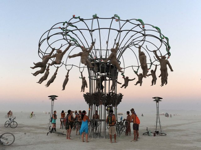 People bang on drums to make monkey effigies spin in an interactive sculpture at the Burning Man festival in Gerlach, Nev. on Friday, Aug. 30, 2013. Once a year, tens of thousands of participants gather in Nevada's Black Rock Desert for the counterculture event. (Photo by Andy Barron/AP Photo/Reno Gazette-Journal)