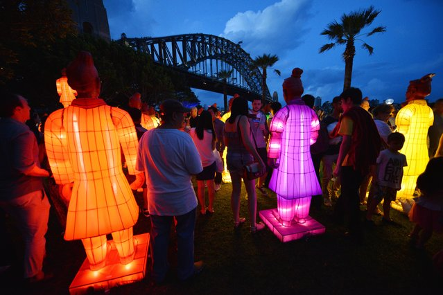 Visitors look at lanterns in the shape of the Chinese Terracotta Warriors at Sydney Harbour on February 13, 2015. The artworks, created for the Beijing Olympic Games in 2008 by a team of Chinese artists, including Xia Nan is on display for the first time in Australia to launch the Australian celebrations of the Lunar New Year of the Sheep. (Photo by Peter Parks/AFP Photo)