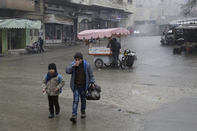 Boys drink traditional Sahlab drinks as they walk along a street during cold weather in the rebel-controlled area of Maaret al-Numan town in Idlib province, Syria January 4, 2016. (Photo by Khalil Ashawi/Reuters)