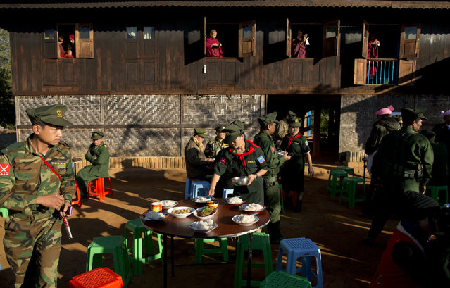 In this Jan. 12, 2015 photo, monks take pictures with their mobile phone cameras as a female officer of the Ta'ang National Liberation army (TNLA) prepares breakfast for visiting rebel leaders at Mar Wong Village in northern Shan state, Myanmar, to mark the 52nd anniversary of their insurrection. (Photo by Gemunu Amarasinghe/AP Photo)