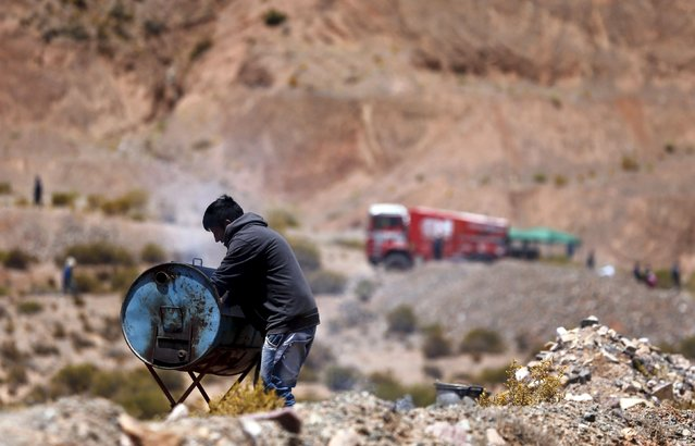 A man cooks on a grill made out of a gasoline tank as a truck arrives at the starting line of the fourth stage of the Dakar Rally 2016 in Jujuy province, Argentina, January 6, 2016. (Photo by Marcos Brindicci/Reuters)