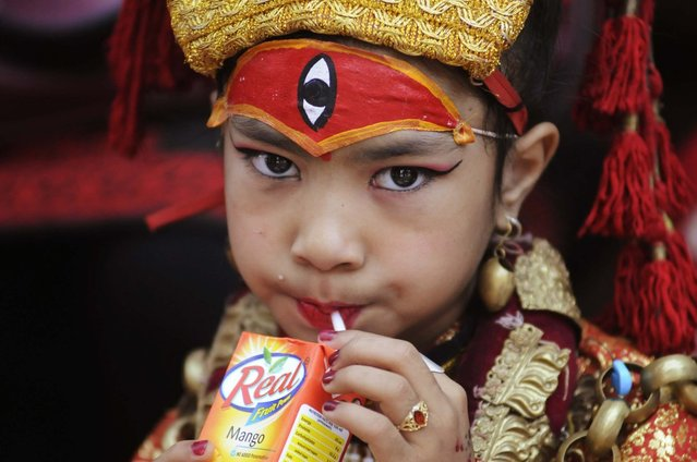 A Nepalese girl wearing a traditional attire drinks juice during the Kumari Puja, a mass worship, at Hanuman Dhoka in Durbar Square in Kathmandu, September 17, 2013. A total of 504 girls under the age of nine from across the country gathered for the mass worship, which is believed to protect them from evil and bring them good luck in future. (Photo by Bikash Dware/Reuters)