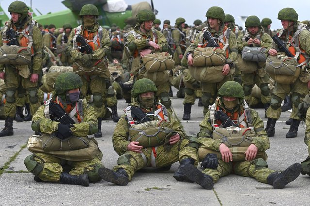Russian paratroopers wait to be load into a plane for airborne drills during maneuvers in Taganrog, Russia, Thursday, April 22, 2021. Russia's defense minister on Thursday ordered troops back to their permanent bases following massive drills amid tensions with Ukraine, but said that they should leave their weapons behind in western Russia for another exercise later this year. (Photo by AP Photo/Stringer)