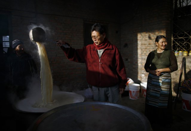 A Tibetan man stirs butter tea made for the arriving guest during the function organised to mark Losar or the Tibetan New Year at a Tibetan Refugee Camp in Lalitpur February 19, 2015. (Photo by Navesh Chitrakar/Reuters)