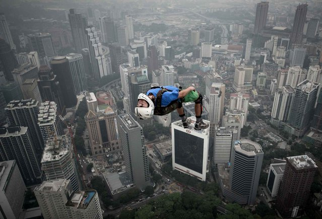 Base jumper Denis Odintsov from Russian leaps from the 300-meters Open Deck of the Malaysia's landmark Kuala Lumpur Tower during the International Tower Jump in Kuala Lumpur on September 27, 2013. Some 103 professional base jumpers from 20 countries are taking part in the annual event. (Photo by Mohd Rasfan/AFP Photo)