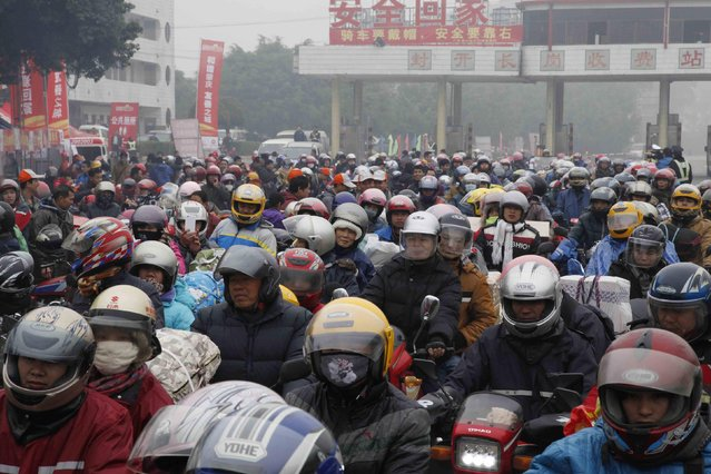 Migrant workers ride their motorcycles with families and friends, as they past a checkpoint on their way home for the upcoming Spring Festival, on a hazy day in Fengkai county, Guangdong province, February 12, 2015. (Photo by Reuters/Stringer)