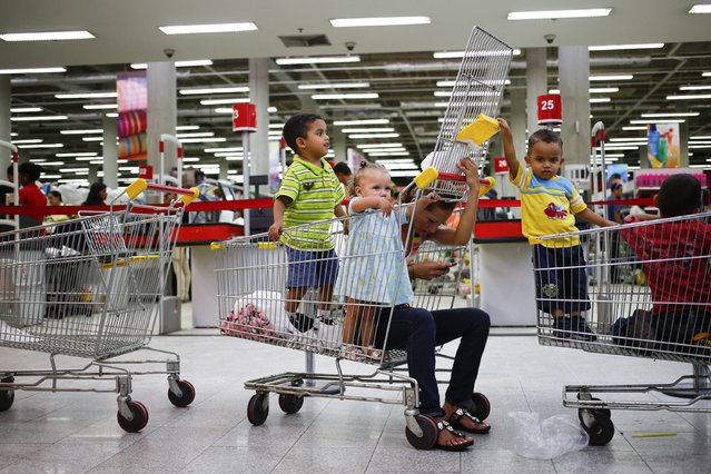 A customer uses a mobile phone while sitting inside a shopping trolley next to children at a state-run Bicentenario supermarket in Caracas, May 2, 2014. (Photo by Jorge Silva/Reuters)