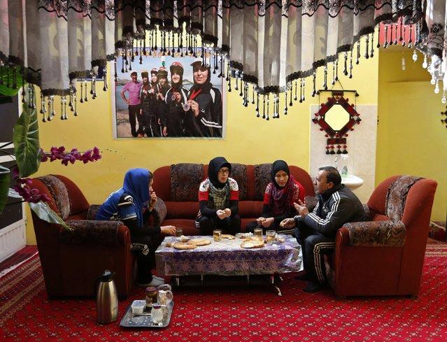 Frozan Rasooli (L), Zahra Alizada (2nd L), and Masooma Alizada (3rd-L) members of  Afghanistan's Women's National Cycling Team, have breakfast with their coach Abdul Sadiq Sadiqi (R) in Kabul February 20, 2015. (Photo by Mohammad Ismail/Reuters)