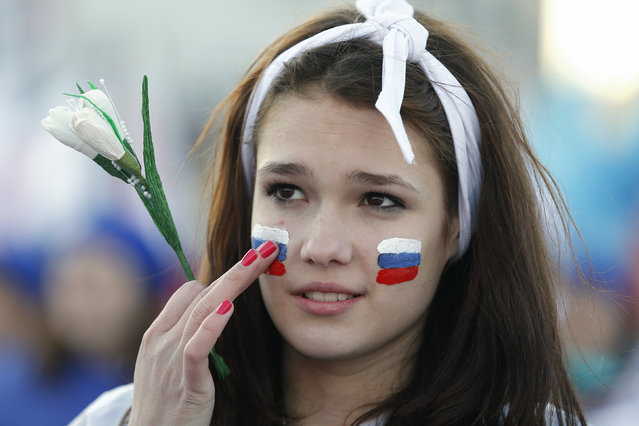 A girl with Russian national flags painted on her cheeks takes part in celebrations marking the first anniversary of Russia's annexation of Crimea, in central Simferopol March 16, 2015. (Photo by Maxim Shemetov/Reuters)