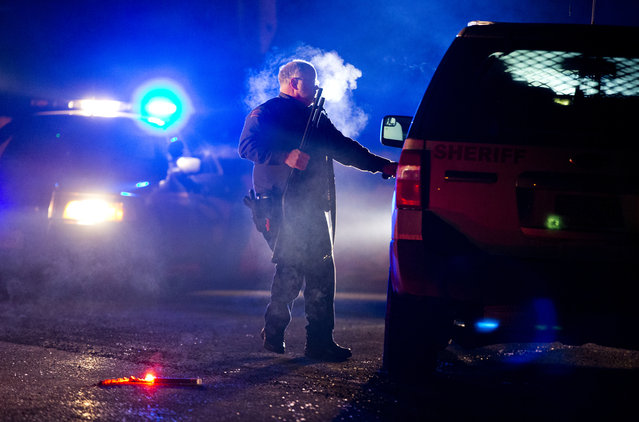A Oregon State police officer stands by a vehicle as police officers block Highway 395 in Seneca, Ore., Tuesday, January 26, 2016. Authorities said shots were fired Tuesday during the arrest of members of an armed group that has occupied a national wildlife refuge in Oregon for more than three weeks. (Photo by Dave Killen/The Oregonian via AP Photo)