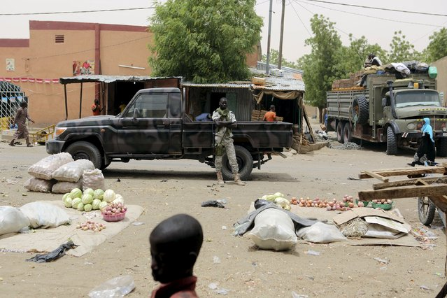 A soldier stands guard in front of a military pickup truck at the main market of Diffa, March 23, 2015. (Photo by Joe Penney/Reuters)