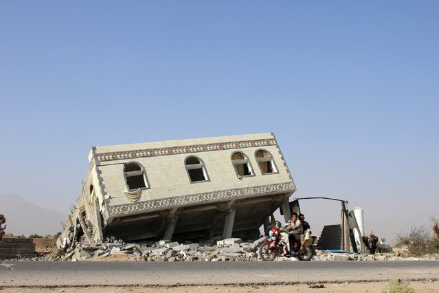 YEMEN: People ride a motorbike past a collapsed building after it was hit by a Saudi-led air strike in the northwestern city of Saada, Yemen November 26, 2016. (Photo by Naif Rahma/Reuters)