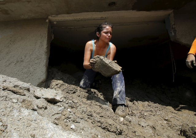 A woman removes a rock from her house after a massive landslide in Chosica, March 24, 2015. (Photo by Mariana Bazo/Reuters)